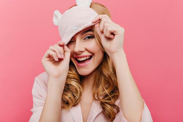 Extatische blonde dame die vroeg in de ochtend pret heeft. charmant europees meisje in grappig oogmasker dat op roze muur lacht.