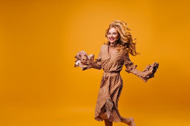 Extatische blonde vrouw in vintage jurk springen zorgeloze elegante dame in bruine outfit dansen op gele muur.