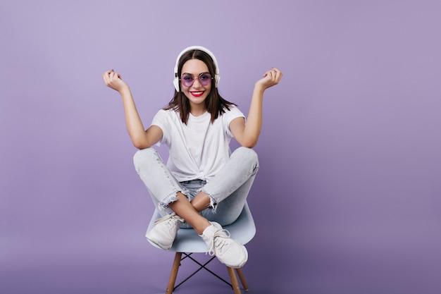 Extatische bruinharige dame grappig poseren tijdens het luisteren naar favoriete liedje. binnen schot van mooi europees meisje in witte outfit, zittend op een stoel.