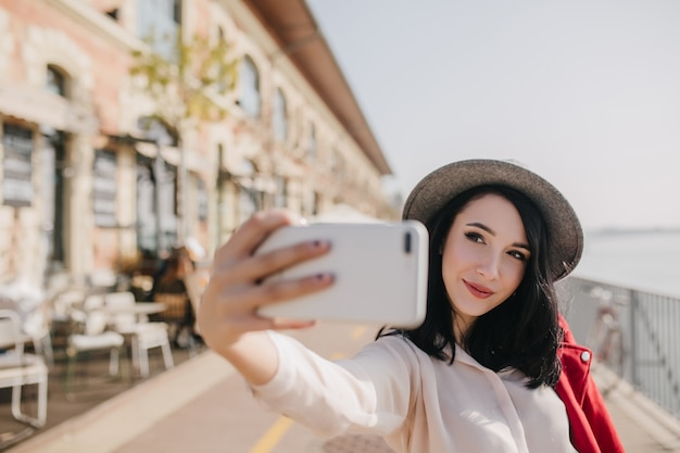 Extatische brunette dame speels poseren op straat in zonnige dag