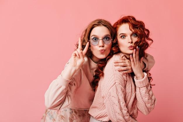 Extatische europese meisjes die vredesteken tonen. studio die van twee dromerige dames is ontsproten die op roze achtergrond omhelzen.