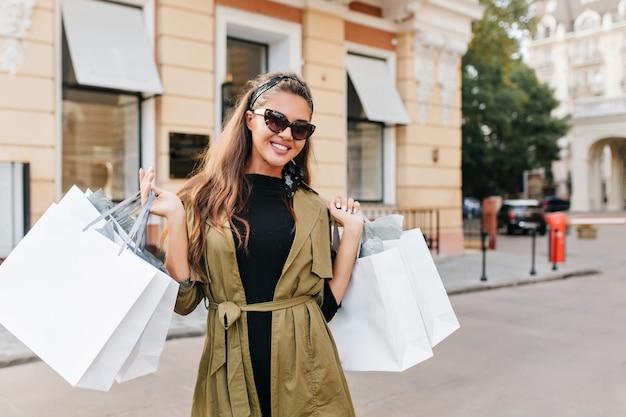 Extatische fashionista-dame draagt trendy jas en poseert met witte pakketten uit de winkel