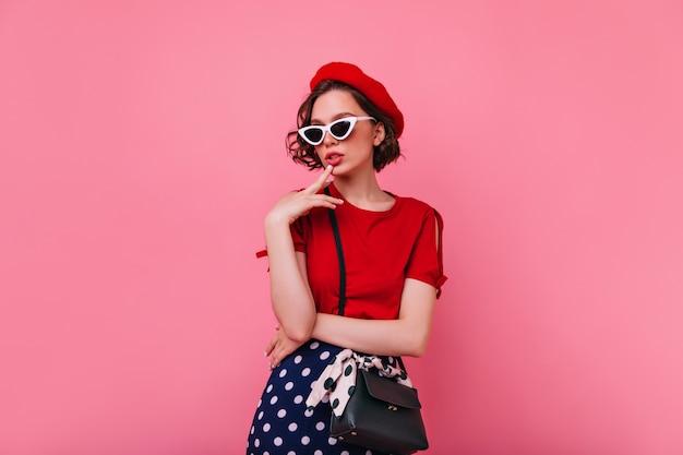 Extatische franse dame met kort kapsel poseren. zelfverzekerd europees vrouwelijk model in rode t-shirt status.