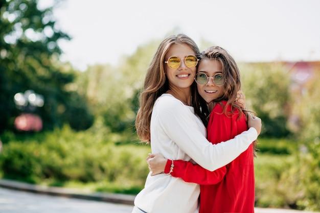 Extatische gelukkige beste vrienden die buiten knuffelen. geïnspireerde jonge vrouw gekleed in lichte truien en zonnebrillen tijd tpgether doorbrengen