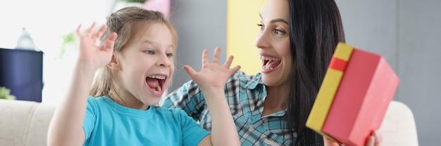 Extatische gelukkige moeder met dochter houdt geschenkdoos close-up
