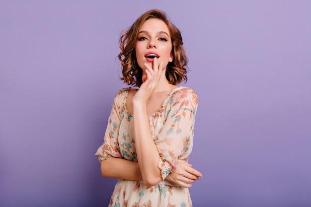 Extatische glamoureuze vrouw met trendy make-up genieten van fotoshoot op paarse achtergrond
