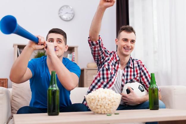 Extatische jonge mannen die voetbal thuis steunen