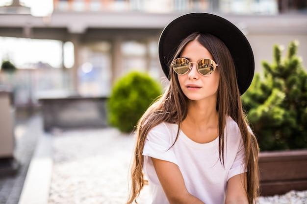 Extatische jonge vrouw die in hoed in openlucht op de bank zit