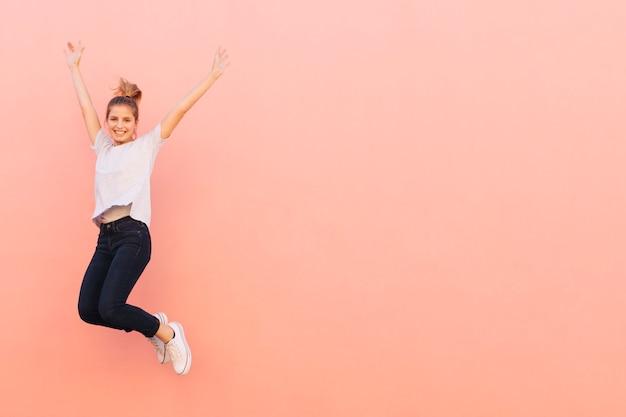 Extatische jonge vrouw die met haar die wapens springen tegen perzik gekleurde achtergrond worden opgeheven