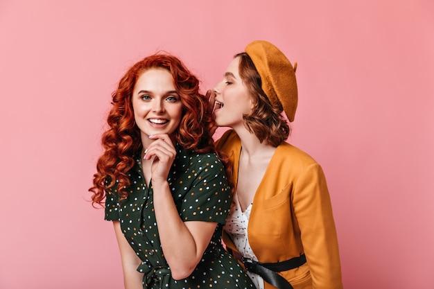 Extatische jonge vrouwen praten op roze achtergrond. studio shot van twee vrienden in vintage outfit.