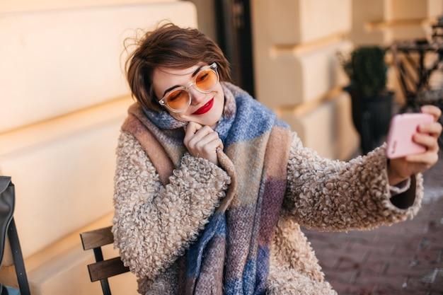 Extatische kortharige vrouw die selfie op straat