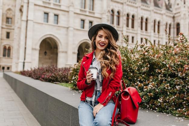 Extatische krullende vrouw in rode jas koffie drinken voor prachtige oude gebouw