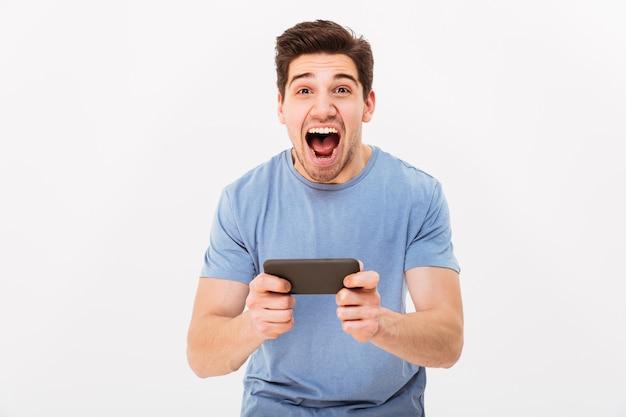 Extatische man in casual t-shirt winnen tijdens het spelen van online games op mobiele telefoon, geïsoleerde over witte muur