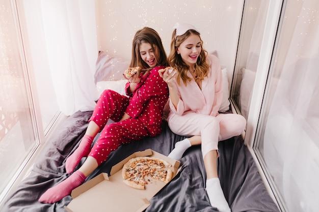 Extatische meisjes in sokken die op zwart blad zitten en pizza eten. binnenportret van prachtige kaukasische dames die van italiaans eten genieten.