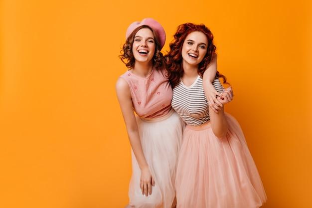Extatische vrienden omarmen op gele achtergrond. betoverende meisjes in goed humeur lachen om de camera.
