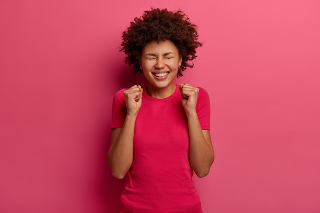 Extatische vrolijke vrouw maakt vuist hobbel, voelt zich erg gelukkig, verheugt zich op succes en triomf, viert veel geld in loterijen, sluit ogen, gekleed in roze kleren, poseert binnen. overwinning behaald