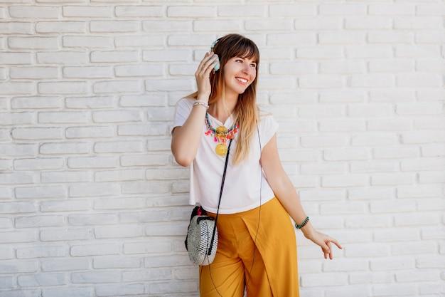 Extatische vrouw genieten van favoriete muziek door oortelefoons, dansen en plezier tonen.