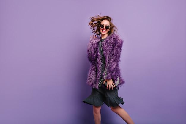 Extatische vrouw in jurk en pluizig jasje dansen met lach