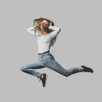 Extatische vrouw met koptelefoon springen in de lucht