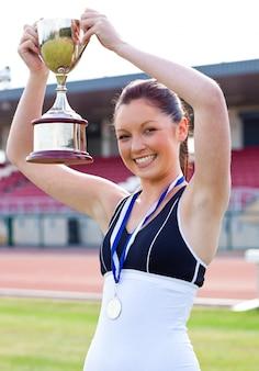 Extatische vrouwelijke atleet die een trophee en een medaille houdt