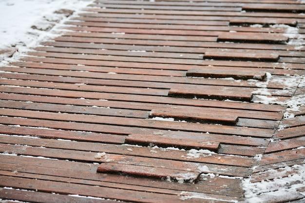 Exterieur houten vlonder bedekt met sneeuw. houten hellingbaan op speelplaats met antislip dwarsbalken