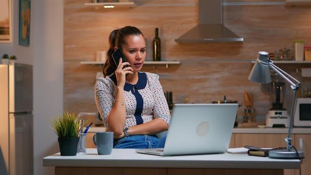 Externe medewerker die aan de telefoon spreekt terwijl hij 's avonds laat op een laptop werkt. drukke, gefocuste freelancer die gebruik maakt van moderne technologienetwerken die overuren maken voor het lezen van een baan, schrijven, zoeken en pauze nemen
