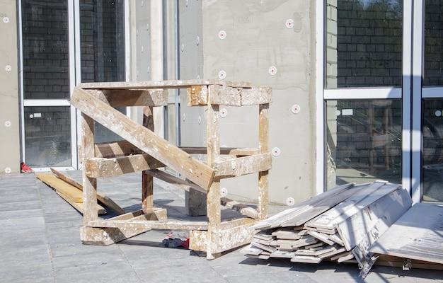 Externe thermische isolatie van het gebouw op de bouwplaats met geëxpandeerde polystyreenplaten. het proces van werk en de uitgeruste werkplaats van de bouwer met materialen en gereedschappen.