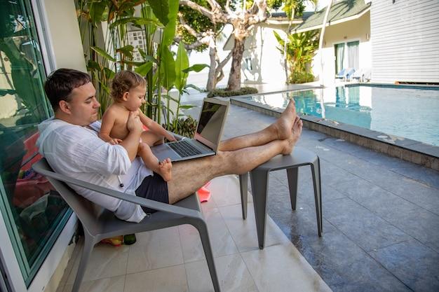 Externe werkman met een peuter in zijn armen met een laptop bij het zwembad in een tropisch land