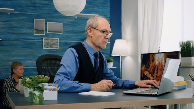 Externe zakenman van middelbare leeftijd die thuis op een laptop werkt en aantekeningen maakt op een notebook in het moderne leven ...