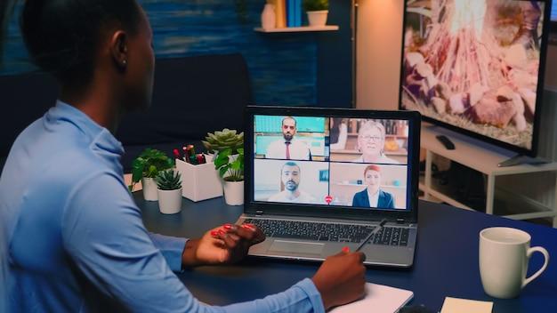Externe zwarte werknemer met videoconferentie die 's avonds laat vanuit huis in de woonkamer werkt. freelancer met behulp van technologienetwerk draadloos praten op virtuele vergadering om middernacht overuren maken