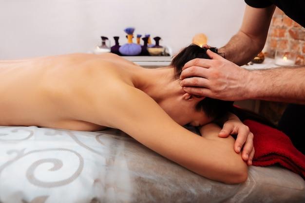 Extra opletten. actieve professionele meester zet zijn werk voort naar het hoofdgebied en masseert nek en nek