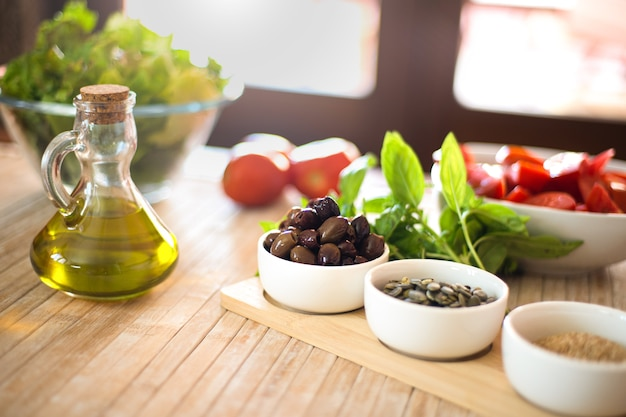 Extra vierge olijfolie en olijven op de voorgrond met verse groenten en zonlicht op de achtergrond - mediterraan dieetconcept