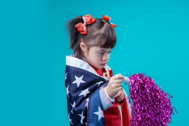 Extravagante accessoires. nieuwsgierig donkerharig meisje met het syndroom van down bezig met 4 juli-versiering in haar handen
