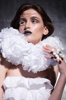 Extravagante halloween-afbeelding van een jonge blanke dame gekleed in een witte jurk met een enorme kraag.