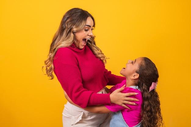 Extraverte zussen maken poses en uitdrukkingen op gele achtergrond op de dag van de broer. broer's dag concept