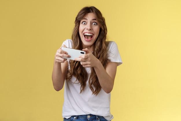 Extreem blij opgewonden speels meisje gamer die geweldig geweldig nieuw smartphonespel speelt houd mobiele telefoon horizontaal juichend kijken camera verbaasd onder de indruk verslaan record gele achtergrond