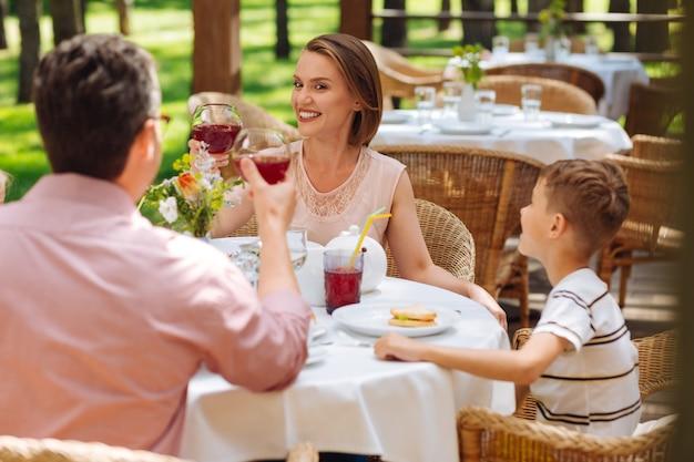 Extreem blij. stralende aantrekkelijke vrouw die zich buitengewoon gelukkig voelt tijdens de lunch met haar gezin