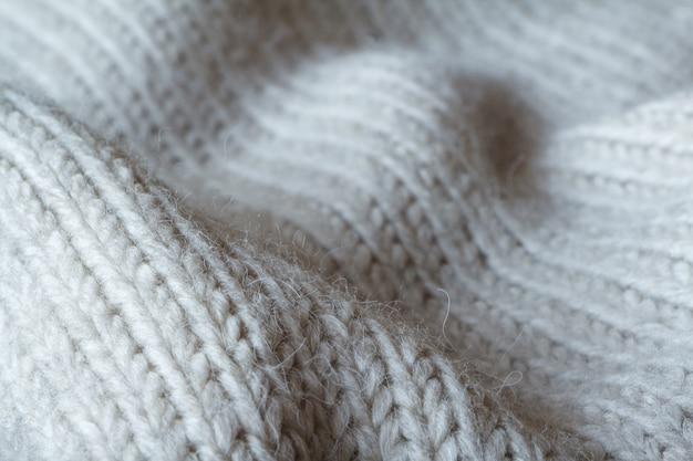 Extreem close-up grijze kleur gebreide trui gemaakt van natuurlijke wollen textuur, golvende plooien