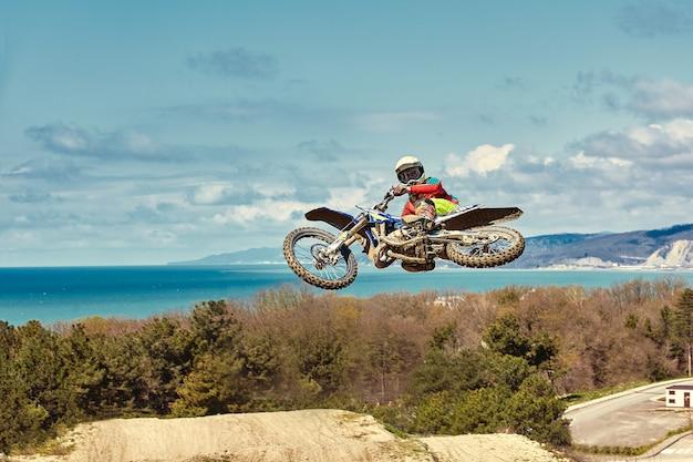 Extreem concept, daag jezelf uit. extreme sprong op een motorfiets met blauwe lucht met wolken. kopieer ruimte, alles of niets.