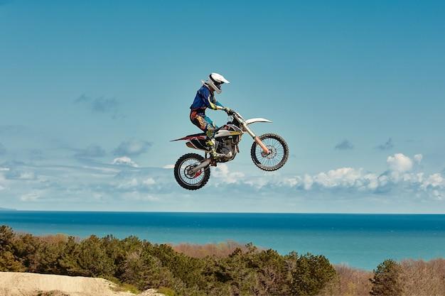 Extreem concept, daag jezelf uit. extreme sprong op een motorfiets op een achtergrond van blauwe lucht met wolken. kopieer de ruimte, alles of niets.