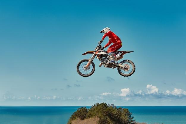 Extreem concept, daag jezelf uit extreme sprong op een motorfiets over blauwe lucht met wolken