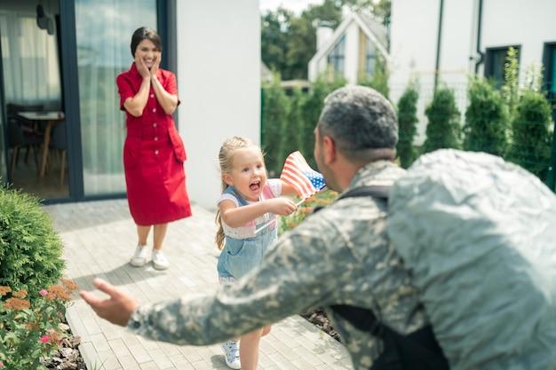 Extreem emotioneel. schattige kleine dochter voelt zich extreem emotioneel als ze papa ziet na militaire dienst