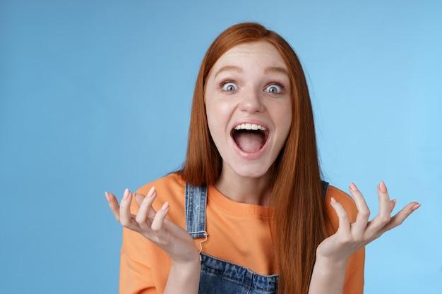 Extreem gelukkig knap kaukasisch roodharig meisje reageert geweldig fantastisch nieuws schreeuwen opgewonden handen opsteken geamuseerd schudden gelukkig schreeuwen ja kijk verbaasd verbaasd blauwe achtergrond