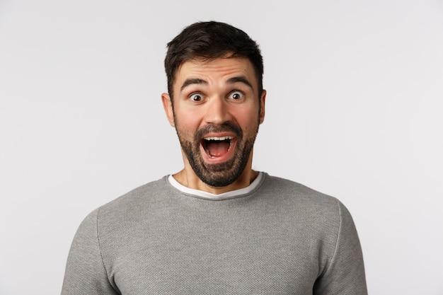 Extreem gelukkige en vrolijke knappe bebaarde blanke man in grijze trui, open mond gefascineerd, zeg wauw verbaasd en geamuseerd