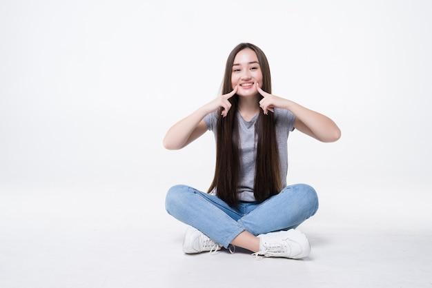 Extreme close-up portret van schattige jonge vrouw wijzend op rimpels onder de wang zittend op de vloer geïsoleerd op een witte muur.