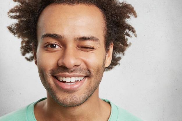 Extreme close-up van de knappe man van gemengd ras heeft trendy kapsel, lacht aangenaam en knippert in de ogen
