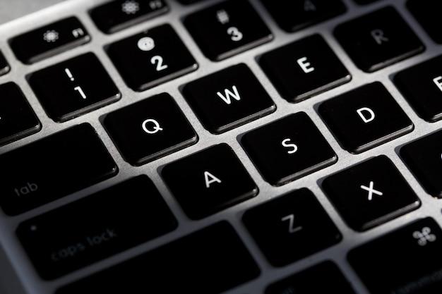 Extreme close-up van een modern zilveren toetsenbord met zwarte knoppen
