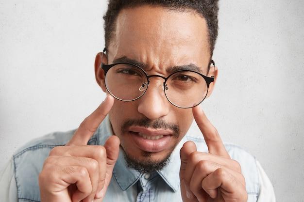 Extreme close-up van gemengd ras ernstige afro-amerikaanse man met snor en baard houdt wijsvinger vooraan