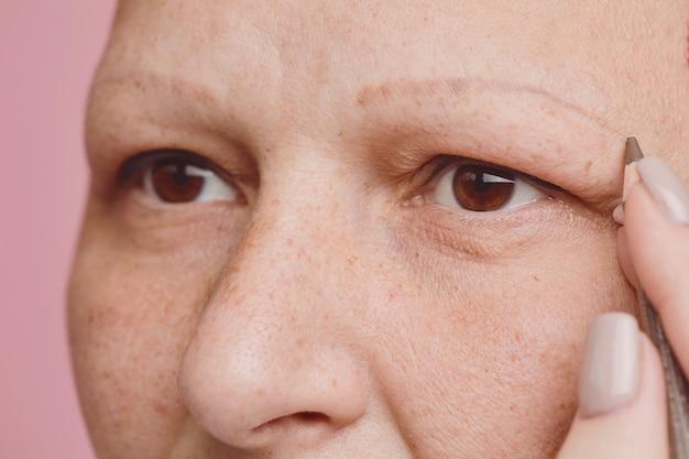 Extreme close-up van sproeten kale vrouw wenkbrauwen tekenen en make-up doen tegen roze achtergrond in studio, alopecia en kanker bewustzijn, kopie ruimte