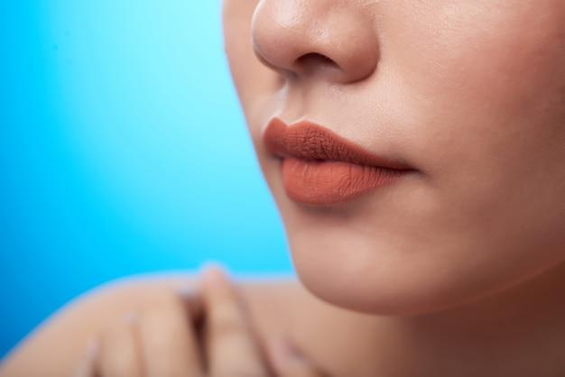 Extreme close-up van vrouwelijke mond met lippenstift, neus en vingers wat betreft blote schouder, op blauw